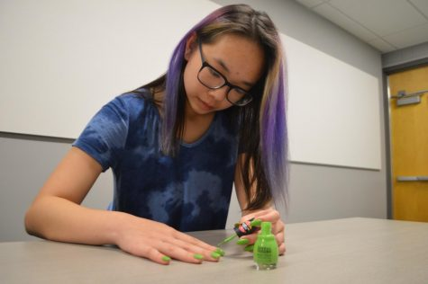 Senior Jackie Yeung paints on a coat of green, sneaker-textured nail polish.