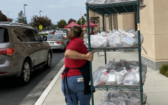 While Fremont High School experiences heavy car traffic, Food Services Assistant Santa Gurrola wheels a cart of packaged meals to the meal pick up location.