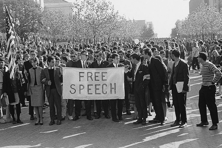 A group of people bring Free Speech signs to a University Hall on November 20, 1964