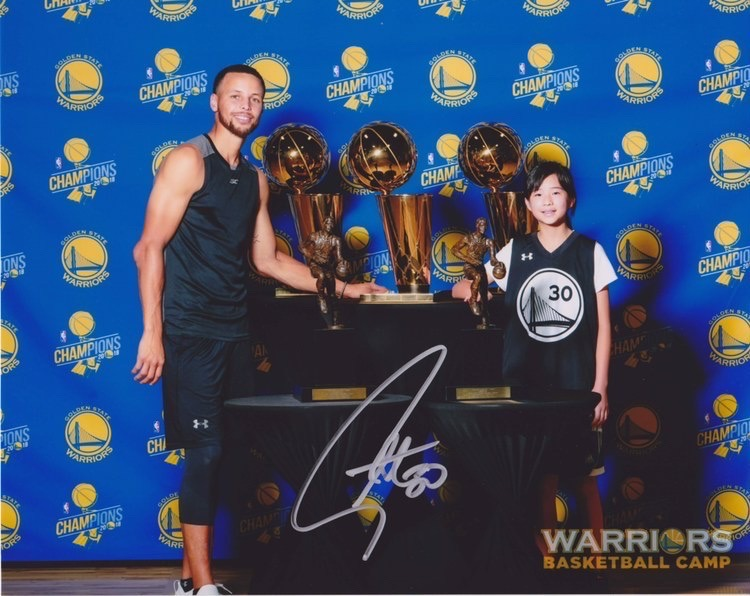 Tang poses for a photo with Curry at Warriors Basketball Camp surrounded by various championship and MVP trophies.