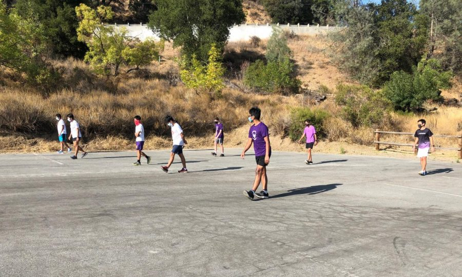 "The male runners on the Cross Country Team maintain social distancing and wear masks during their drills at Stevens Canyon near the reservoir. The team often runs there for ""maintenance"" days to get extra mileage."