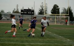 Senior Skylar Ploshay dribbles the ball across the field.