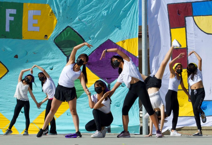 A heart formation signals the end of the girls dance performance. The freshmen skit represents a gameshow adaptation of the Game of Life board game, following four characters through different stages of their adventure. The dance ushers in the next advancement of the game — shopping for homes.