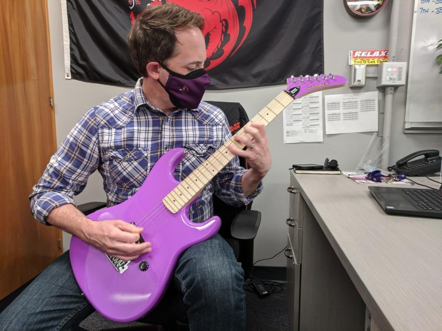 Scott Victorine pulls out a purple guitar from his small collection he has in closet during tutorial to play.