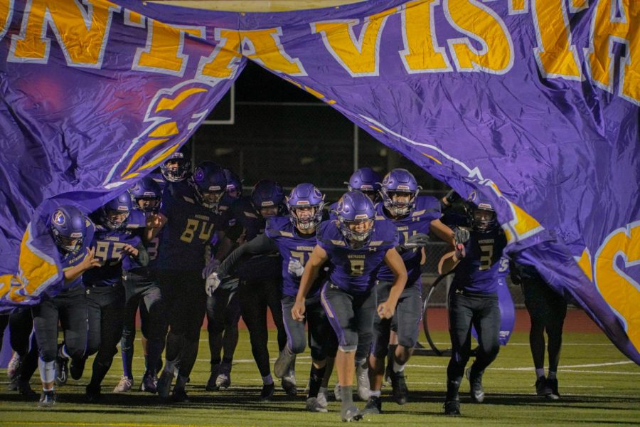 The team rushes through the banner, marking the end of halftime and the beginning of the third quarter. Photo by Michelle Zheng