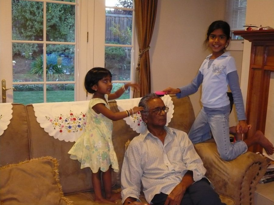 My sister, Samhitha, and I stand on the sofa brushing and playing with our maternal grandpas hair.